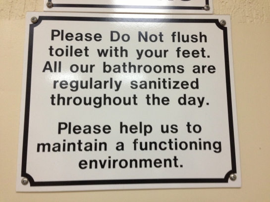 sign in the belize city airport bathroom